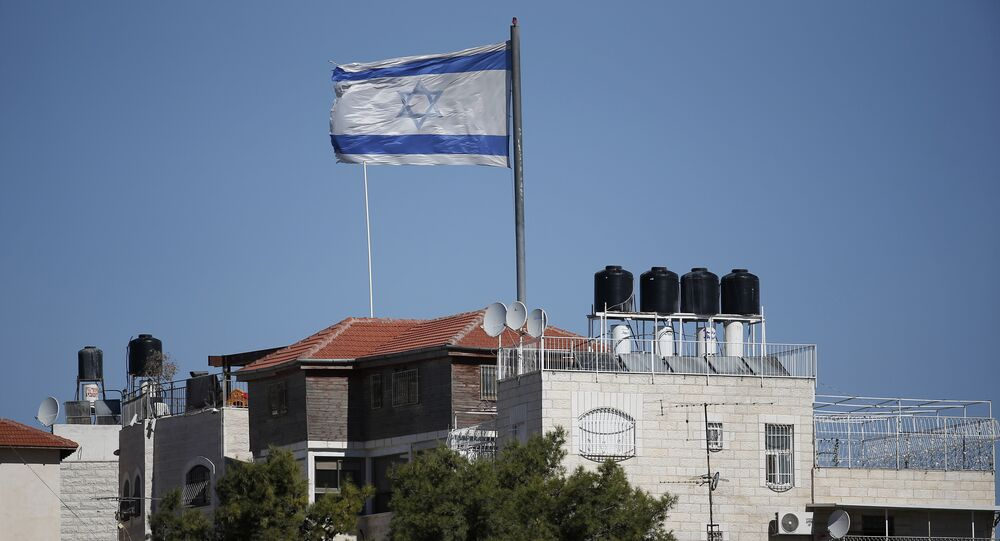 A giant Israeli flag flies over a settlement building situated in the middle of a Palestinian neighbourhood of Al-Tur in East Jerusalem, on November 11, 2014