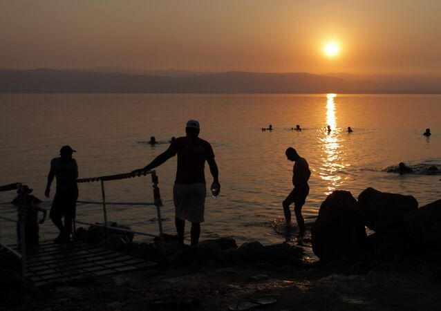 Tourists and local residents visit the Dead Sea beach, 34 miles (55 kilometers) southeast of Amman, Jordan, Friday, June 29, 2012