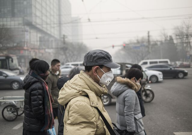 This file photo shows pedestrians wear masks on a polluted day in Beijing on November 30, 2015