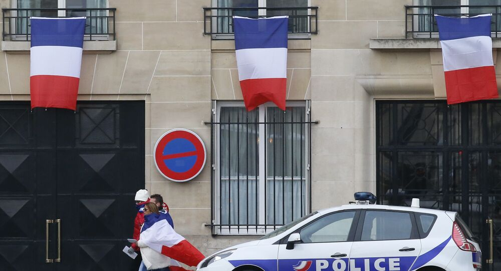 People drapped in the national flag walk past a building decorated with French flags in Paris, Friday, Nov. 27, 2015.