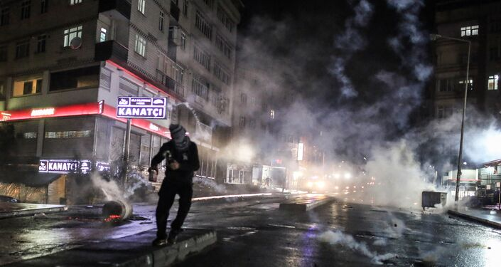 Police use teargas to disperse masked militants protesting the killing of Tahir Elci, a prominent lawyer and human rights defender, who faced a prison term on charges of supporting Kurdish rebels, in Istanbul, Turkey, late Saturday, Nov. 28, 2015