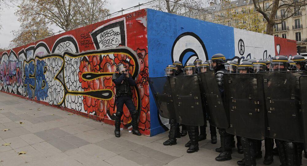 Policemen prepare for an assault by demonstrators during a protest ahead of the 2015 Paris Climate Conference at the place de la Republique, in Paris, Sunday, Nov. 29, 2015.