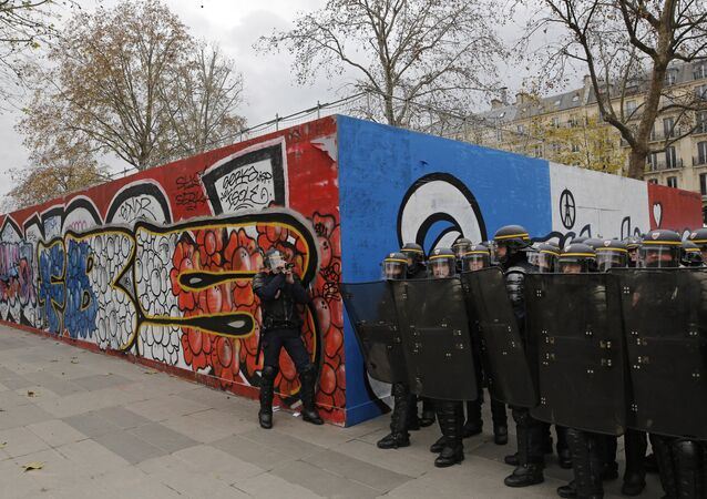 Policemen prepare for an assault by demonstrators during a protest ahead of the 2015 Paris Climate Conference at the place de la Republique, in Paris, Sunday, Nov. 29, 2015.
