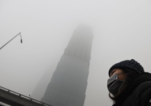 A woman waits for a bus below a skyscraper shrouded in smog on a heavily polluted day in Beijing on December 1, 2015