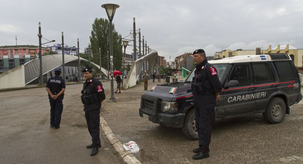 Kosovo police and Italian Carabineri stand near remains of a roadblock dismantled by Serbs in the tense city of Mitrovica Kosovo on Wednesday, June 18, 2014