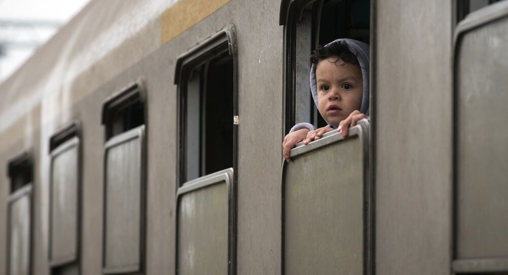A child looks from a train carrying migrants in Kljuc Brdovecki, Croatia, near the Slovenian border, Friday, Oct. 23, 2015.