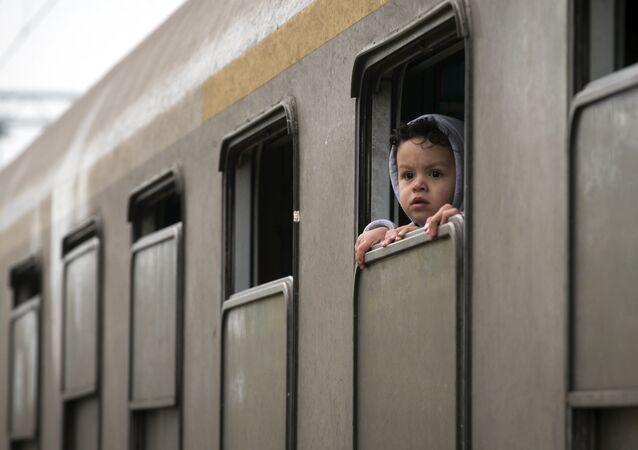 A child looks from a train carrying migrants in Kljuc Brdovecki, Croatia, near the Slovenian border, Friday, Oct. 23, 2015.