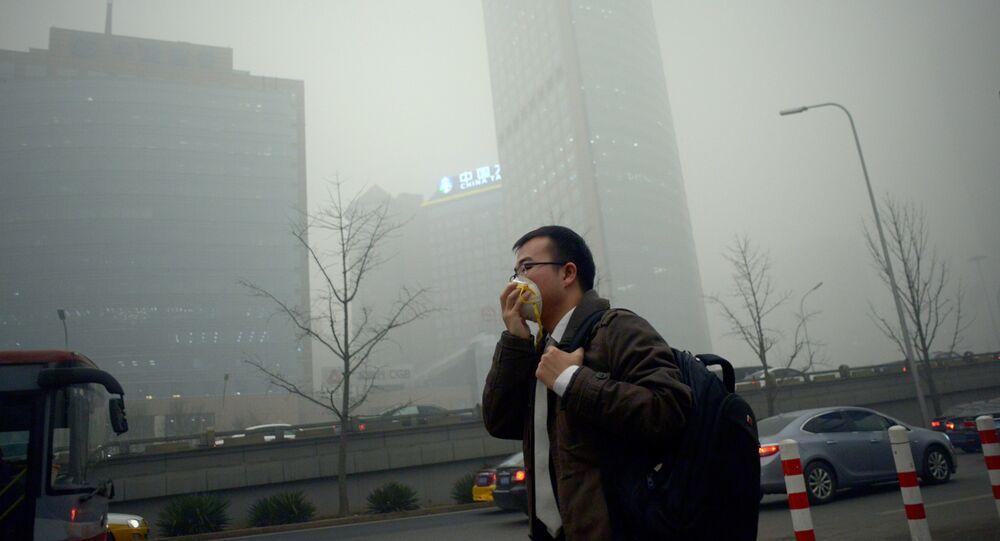 A man wearing a mask walks along a road in heavy pollution in Beijing on December 1, 2015
