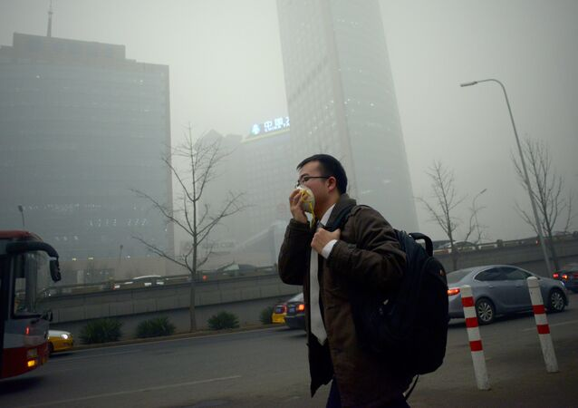 A man wearing a mask walks along a road in heavy pollution in Beijing on December 1, 2015