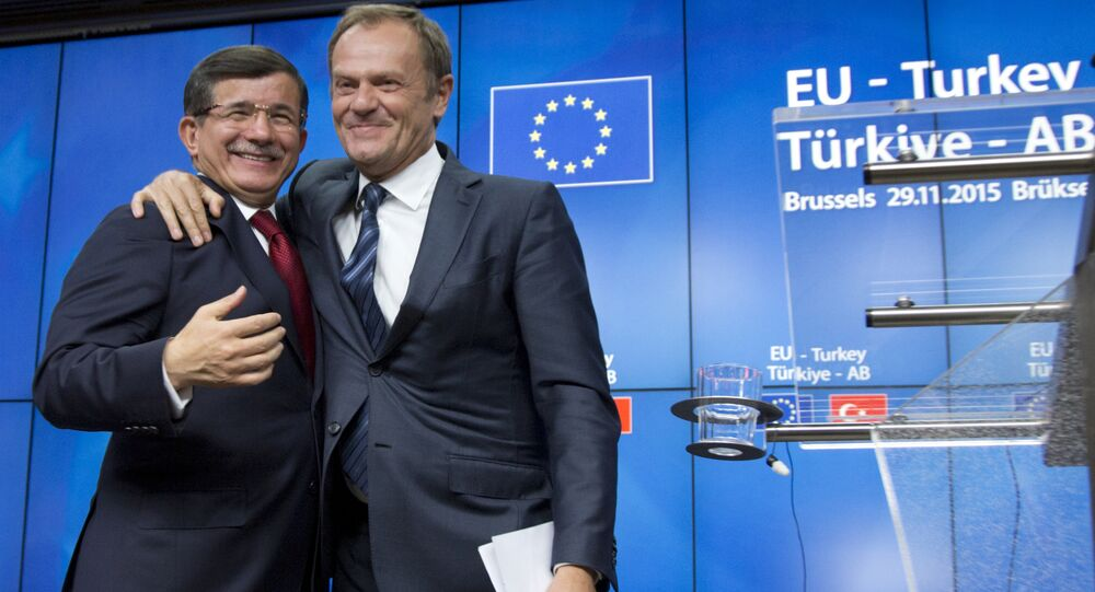 European Council President Donald Tusk, right, puts his arm on the shoulder of Turkish Prime Minister Ahmet Davutoglu after a media conference at an EU-Turkey summit in Brussels on Sunday, Nov. 29, 2015.