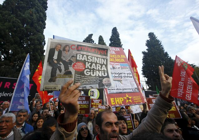 A demonstrator holds newspaper read Black day of the press during a protest outside the Cumhuriyet newspaper in Istanbul, Turkey, November 27, 2015