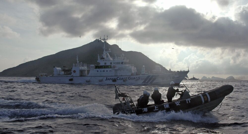 In this Sunday, Aug. 18, 2013 file photo, Japanese Coast Guard boat and vessel sail alongside Japanese activists' fishing boat, not in photo, warning the activists away from a group of disputed islands called Diaoyu by China and Senkaku by Japan