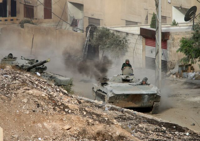 Syrian APC is followed by a tank in Harasta, northeast of Damascus, Syria, Thursday, Oct. 22, 2015