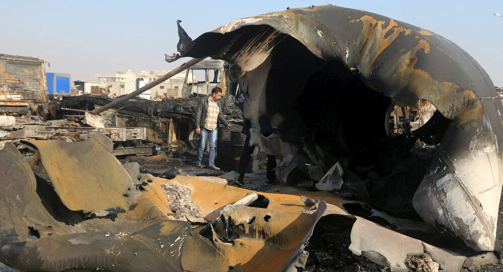 A man inspects the damage after what activists said were air strikes carried out by the Russian air force, on a parking garage for cargo trucks in al-Dana town, near the Syrian-Turkish border in Idlib Governorate November 28, 2015