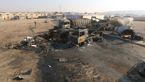 A general view shows damaged trucks after what activists said were air strikes carried out by the Russian air force, on a parking garage for cargo trucks in al-Dana town, near the Syrian-Turkish border in Idlib Governorate November 28, 2015 - Sputnik International