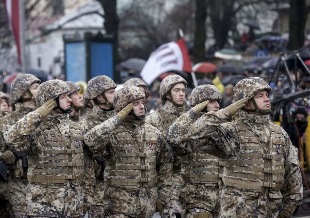 Soldiers from the Latvian army salute as they march during Independence Day military parade in Riga, Latvia, November 18, 2015
