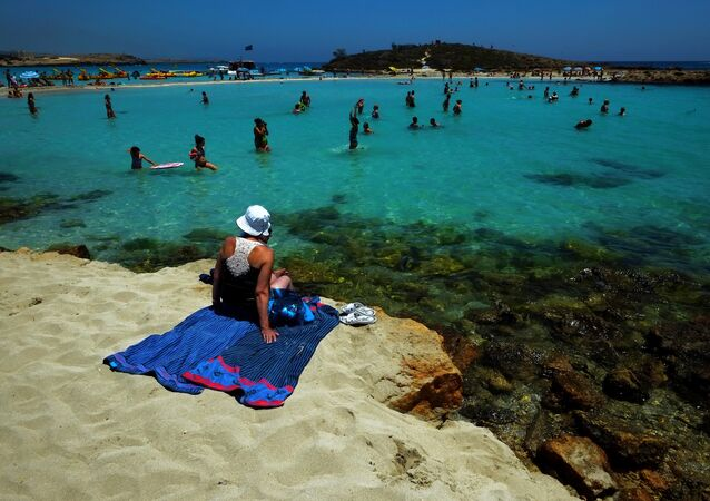 A woman sit on the sand as other people enjoy the sea at Nissi Beach in the famous southeastern coastal resort of Ayia Napa, Cyprus, Saturday, June 14, 2014