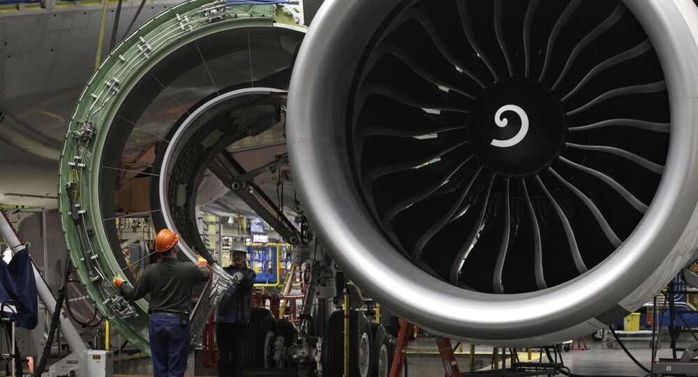 Worker manoeuvres the cover of a engine into place on a Boeing 777 jet at the company's manufacturing plant, Monday, 14 February 2011, in Everett, Washington, US.