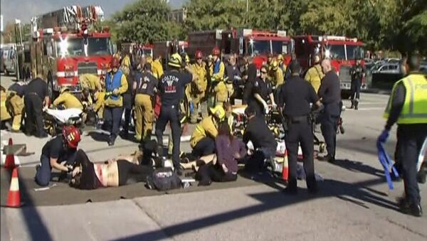 Still from video shows rescue crews tending to the injured in the intersection outside the Inland Regional Center in San Bernardino - Sputnik International