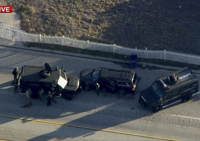 Police armored cars close in on a suspect vehicle following a shooting incident in San Bernardino.