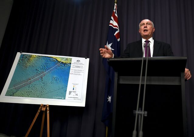 Australia's Deputy Prime Minister Warren Truss speaks during a media conference next to a map displaying the search area for missing Malaysia Airlines Flight MH370 at Parliament House in Canberra, Australia, December 3, 2015