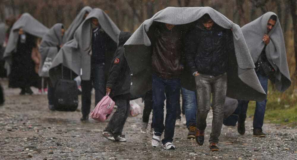 Migrants shield from rain with blankets as they walk after crossing the border from Greece into Macedonia, near Gevgelija, Macedonia, November 27, 2015