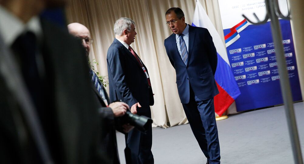 Russian Foreign Minister Sergei Lavrov (R) waits to greet the US Secretary of State prior to a bilateral meeting alongside the annual Organization for Security and Cooperation in Europe (OSCE) Ministerial Council meeting in Belgrade on December 3, 2015