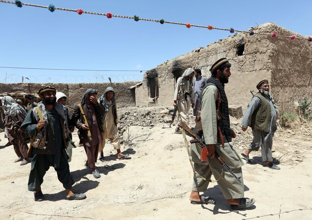 In this Thursday, May 21, 2015 file photo, local militia group fighters walk past a building torched by Taliban fighters at Talawka village in Kunduz province, north of Kabul, Afghanistan