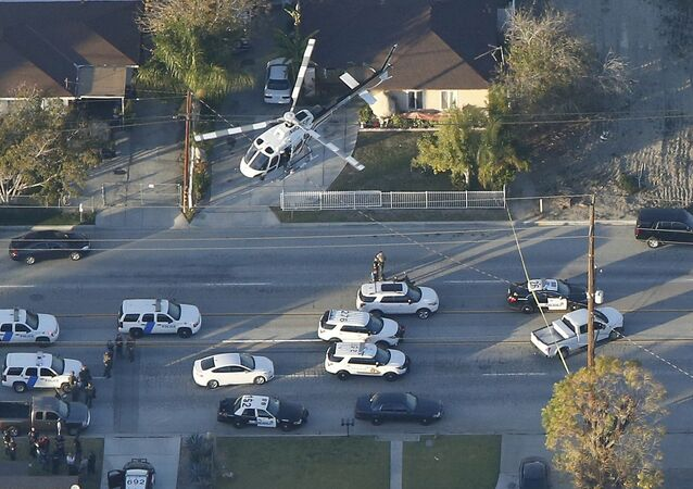 A police helicopter flies over emergency vehicles during a manhunt which followed a mass shooting in San Bernardino, California December 2, 2015