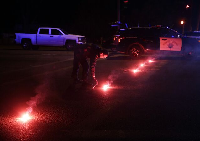 A police officer lights up flares near the scene where a shootout took place, Wednesday, Dec. 2, 2015, in San Bernardino, Calif.