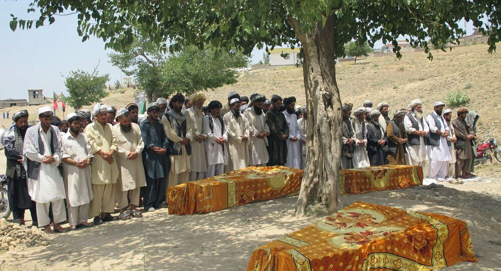 Afghans offer prayers over the covered coffins during a burial ceremony in Khost, Afghanistan.