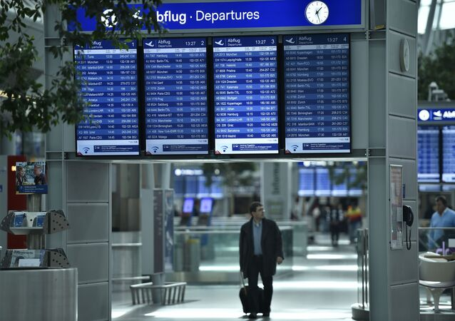 A passengers walks under information boards at the airport in Duesseldorf, Germany