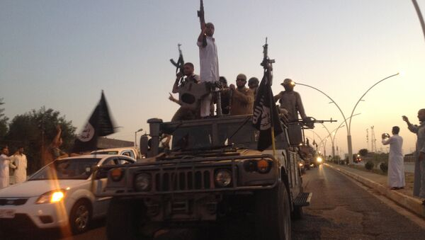 Fighters of the al-Qaida-inspired Islamic State of Iraq and the Levant (ISIL) parade in a commandeered Iraqi security forces armored vehicle down a main road at the northern city of Mosul, Iraq. (File) - Sputnik International