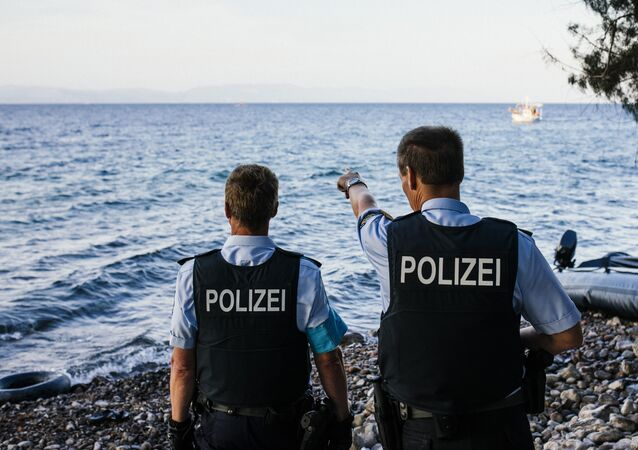 German police officers, representatives of the EU's border management agency Frontex, on the Greek island of Lesbos, look at a dinghy with migrants crossing the Aegean sea from Turkey, on October 17, 2015.