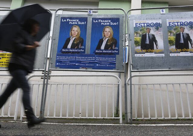 A woman walks past electoral posters of far right National Front party regional leader for southern France, Marion Marechal-Le Pen, left, and French right-wing party Les Republicains candidate Christian Estrosi, in Nice, southeastern France, Saturday, Dec. 5, 2015.
