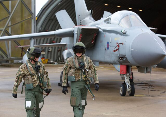 Pilots walk in front of a Tornado GR4 aircraft at the British Royal Air Force airbase RAF Marham in Norfolk in east England on December 2, 2015