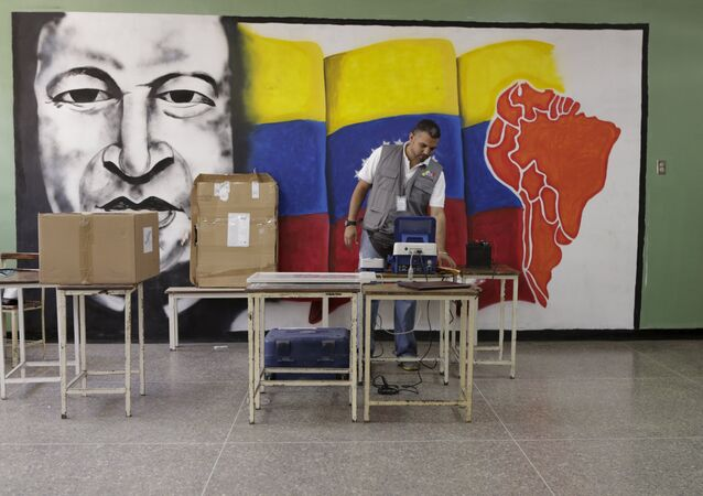A worker of the National Electoral Council (CNE) configures a voting machine in front of a mural depicting Venezuela's late President Hugo Chavez at a school in Caracas, December 4, 2015. Venezuela will hold parliamentary elections on December 6.