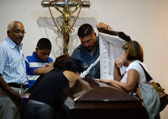 Family attend the funeral of the local leader of the Democratic Action party in Altagracia de Orituco, Luis Manuel Diaz, in the Altagracia de Orituco town in Guarico state, Venezuela, on November 26, 2015.