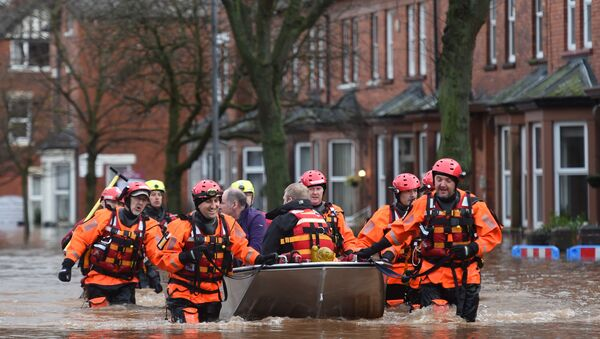Members of the emergency services carry people to safety from a flooded street in Carlisle on December 6, 2015. One man was killed yesterday as Storm Desmond whipped across Britain, bringing heavy rain, strong winds and flooding to parts of the country. - Sputnik International