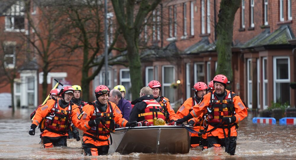 Members of the emergency services carry people to safety from a flooded street in Carlisle on December 6, 2015. One man was killed yesterday as Storm Desmond whipped across Britain, bringing heavy rain, strong winds and flooding to parts of the country.