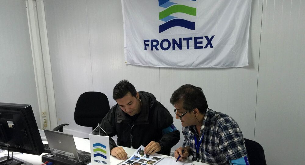In this photo taken on Saturday, Oct. 31, 2015, Frontex officer Francisco Ramos, left, and a colleague review data at a registration center run by the EU border protection agency at Moria on the island of Lesbos in southeastern Greece.