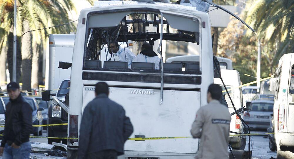 Tunisian forensics police inspect a Tunisian presidential guard bus at the scene of a suicide bomb attack in Tunis, Tunisia