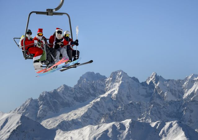 People wearing Santa Claus costumes ride a ski lift on December 6, 2015 above Verbier, Swiss Alps