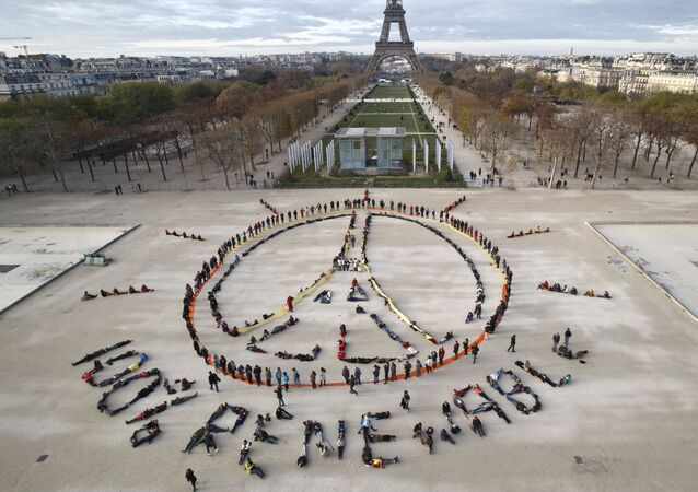 Environmentalist activists form a human chain representing the peace sign and the spelling out 100% renewable, on the side line of the COP21, United Nations Climate Change Conference near the Eiffel Tower in Paris, Sunday, Dec. 6, 2015.