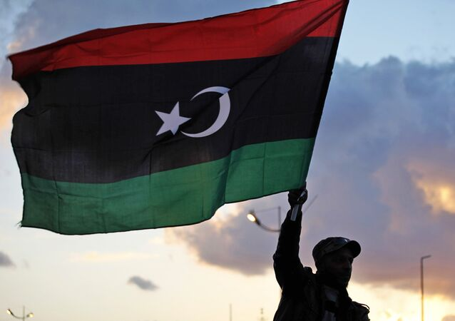 A Libyan waves the national flag