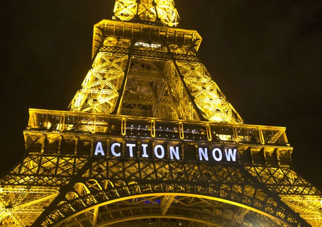 The Eiffel Tower lights up with the sloganAction Nowreferring to the COP21, United Nations Climate Change Conference in Paris, Sunday, Dec. 6, 2015
