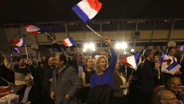 Supporters of far right National Front party regional leader for southeastern France, Marion Marechal-Le Pen, wave flags at a meeting after the results of the first round of the regional elections, in Carpentras, southern France - Sputnik International