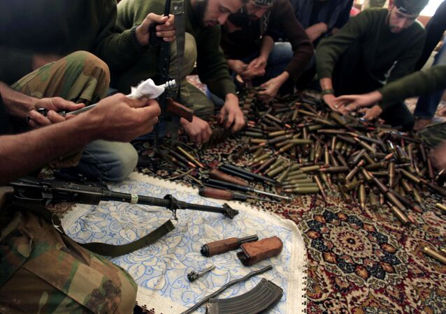 Free Syrian Army fighters clean their weapons and check ammunition at their base on the outskirts of Aleppo, Syria.