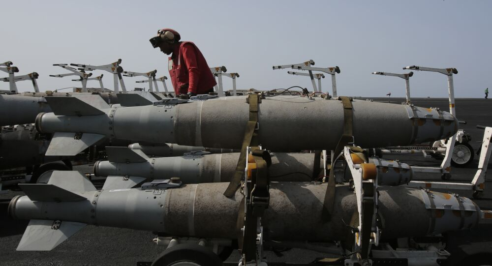 A U.S. sailor works with bombs being prepared for loading on military jets on the flight deck of the USS Carl Vinson aircraft carrier in the Persian Gulf, Thursday, March 19, 2015