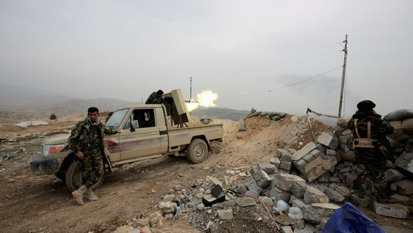 Kurdish peshmerga fighter fires a weapon towards positions of the Islamic State group who are 500 meters or half a mile away, overlooking the strategic town of Sinjar, northern Iraq - Sputnik International